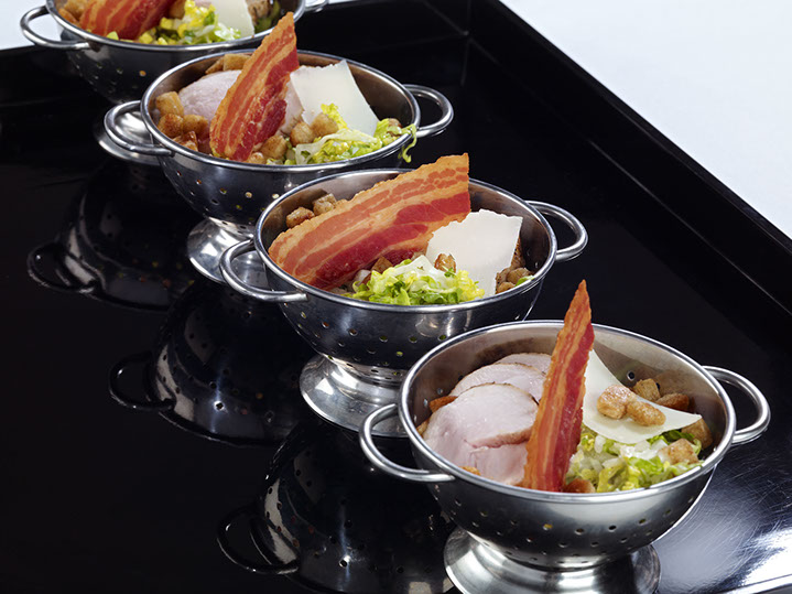 Colanders of chicken and crispy bacon caesar salad