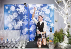 Flair bartender at an alpine themed bar throws a bottle into the air at an aprés ski party