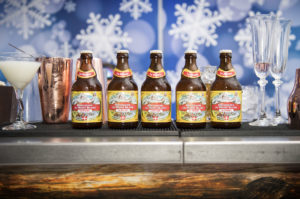 Five beer bottles lined up atop an alpine themed bar at an aprés ski party