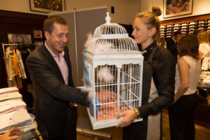 A delegate is served canapes from a large white birdcage by a waitress  at a corporate networking event