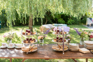 Bare wooden table in a garden with overhanging trees, with cake stands 50th birthday party