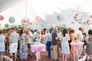 Guests dressed for summer enjoy vintage treats in a marquee for a 50th birthday party