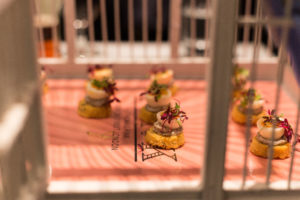 Poached quail egg served with a wild mushroom pate on caraway shortbread served inside a birdcage