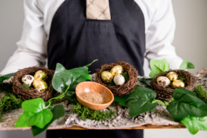 Quails eggs served in nests from a wooden board held by a waitress: wedding spectacular