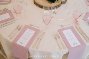 Wedding spectacular: Table set up for wedding breakfast with white table cloth, gold cutlery, pink napkins and menus
