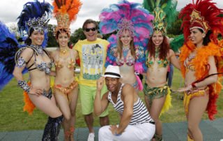 Brazilian dancing girls and guests pose for a photo at a world cup party