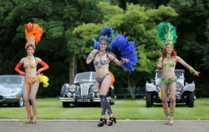 Brazilian carnival dancers perfroming in road in front of classic cars for world cup party