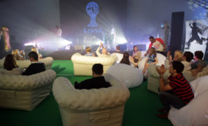Guests relax on comfy sofas in front of a stage with musical equipment on it and a large Brazil flag for a world cup party