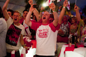 Man in red and white t-shirt celebrates amongst a crowd at a world cup party