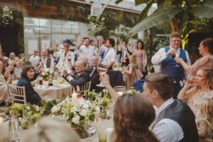 wedding spectacular: a room full of wedding guests, seated, raising glasses to the bride and groom