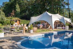 Guests celebrate a 50th birthday party in a marquee beside a swimming pool on a bright summers day